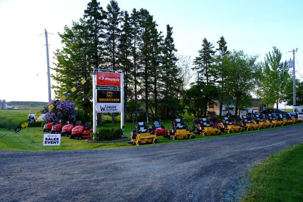 Hustler & Simplicity mowers lined up by the sign